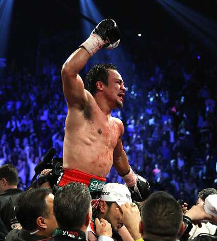 Juan Manuel Marquez celebrates after he knocked out Manny Pacquiao in the 6th round of their welterweight fight on December 8, 2012, at the MGM Grand Garden in Las Vegas, Nevada.  AFP PHOTO / John GurzinskiJOHN GURZINSKI/AFP/Getty Images Photo: John Gurzinski, AFP/Getty Images