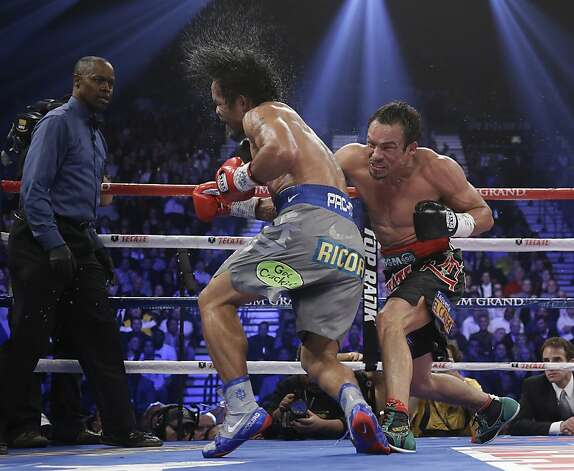Juan Manuel Marquez, from Mexico, right, connects against Manny Pacquiao, from the Philippines, as referee Kenny Bayless looks on at left, during their WBO world welterweight  fight Saturday, Dec. 8, 2012, in Las Vegas. Marquez won the fight by a knockout. (AP Photo/Julie Jacobson) Photo: Julie Jacobson, Associated Press