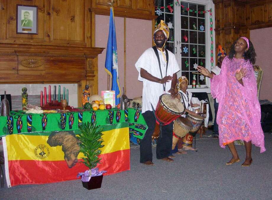 Kojo Bey, left,artistic director for Sounds of Afrika on the drum, his wife Franchone Bey, right. Center, is Khalfani Drakeford , a young drummer. They are  performing during a Kwanzaa celebration last year. Photo: Contributed Photo / The News-Times Contributed