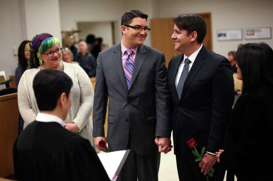 Jesse Page, left, and Brendan Taga, exchange wedding vows just after midnight at the King County Courthouse in Seattle. Marriage ceremonies were held in the courtroom of Superior Court Judge Mary Yu beginning at 12:01 a.m. on Sunday, the first day same-sex couples in Washington State can legally be married. Some commented that the judge had the perfect name to perform the ceremonies. Photo: JOSHUA TRUJILLO / SEATTLEPI.COM