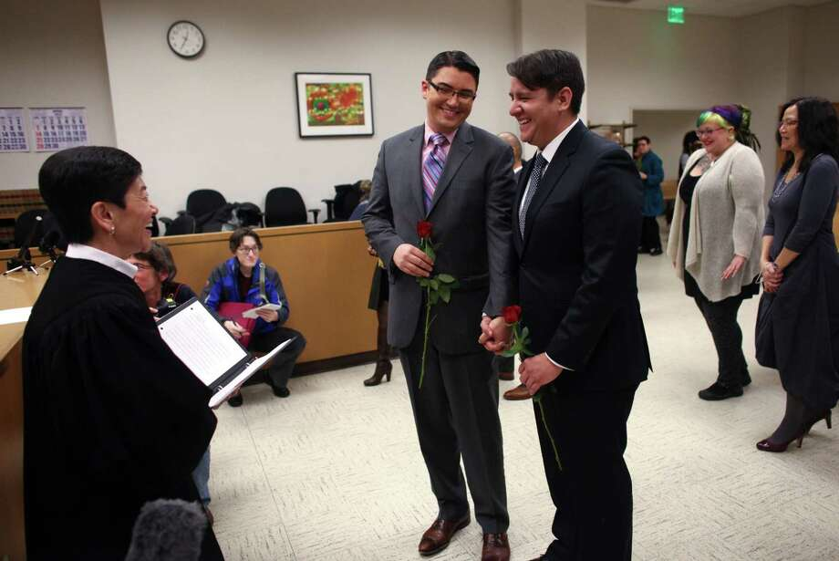 Jesse Page, left, and Brendan Taga, exchange wedding vows just after midnight in the courtroom of Superior Court Judge Mary Yu. Photo: JOSHUA TRUJILLO / SEATTLEPI.COM