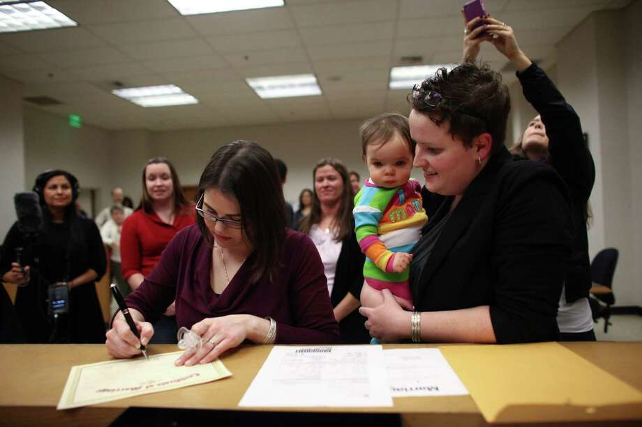 Emily Cofer, left, and her wife Sarah Cofer, both of Arlington, sign their marriage certificate just after midnight at the King County Courthouse in Seattle. Marriage ceremonies were held in the courtroom of Superior Court Judge Mary Yu beginning at 12:01 a.m. Photo: JOSHUA TRUJILLO / SEATTLEPI.COM