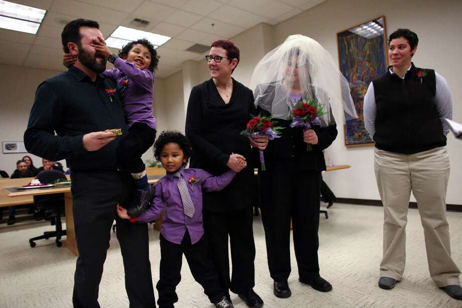 Twins Ari, left, and Raffi, have some fun as their mothers Cynthia Wallace, center, and Julie Fein, with veil, are married just after midnight on Sunday at the King County Courthouse in Seattle. At left is witness Jason Plourde and at right is Shayna Israel. Photo: JOSHUA TRUJILLO / SEATTLEPI.COM