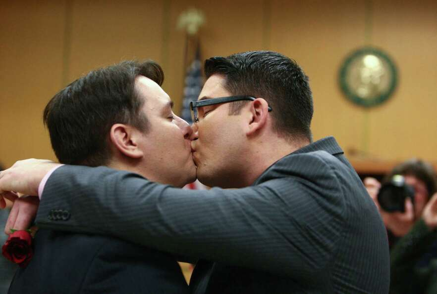 Brendan Taga, left, and Jesse Page kiss as they are married in the courtroom of Superior Court Judge