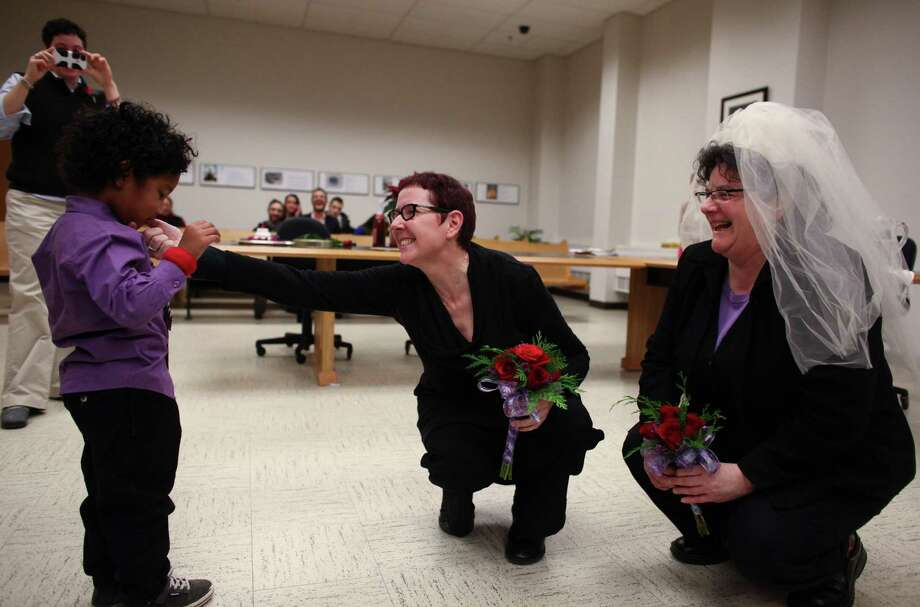 Cynthia Wallace, center, and Julie Fein are handed a ring by their son Rafi during their wedding at the King County Courthouse in Seattle. Marriage ceremonies were held in the courtroom of Superior Court Judge Mary Yu beginning at 12:01 a.m. on Sunday, the first day same-sex couples in Washington State can legally be married. Photo: JOSHUA TRUJILLO / SEATTLEPI.COM