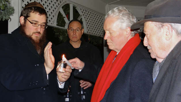 First Selectman Michael Tetreau helps light the first candle on the menorah at the Sherman Green gazebo Saturday flanked by Rabbi Shlame Landa, left, and Joe Macy.  Fairfield CT 12/8/12 Photo: Mike Lauterborn / Fairfield Citizen contributed