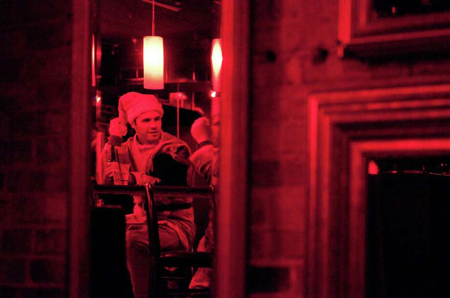 Santas glow red under the lights of Club Noc Noc during SantaCon 2012 in Seattle on Saturday, December 8, 2012.  Photo: LINDSEY WASSON, Lindsey Wasson / SEATTLEPI.COM