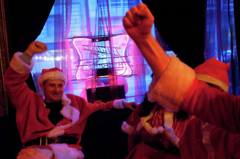 Santas raise their fists and cheer at Club Noc Noc during SantaCon 2012 in Seattle on Saturday, December 8, 2012. Photo: LINDSEY WASSON, Lindsey Wasson / SEATTLEPI.COM