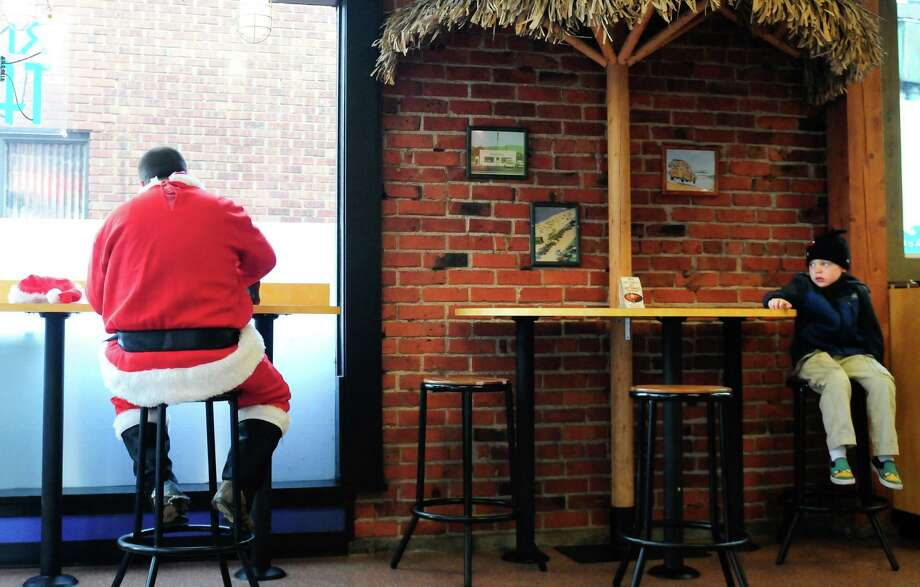 A child eyes a Santa eating at a Taco Del Mar on Cedar St. during SantaCon 2012 in Seattle on Saturday, December 8, 2012.  Photo: LINDSEY WASSON, Lindsey Wasson / SEATTLEPI.COM