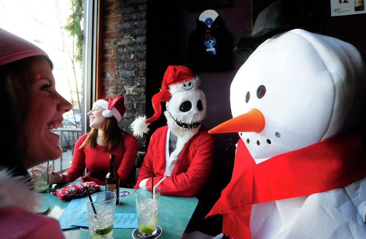 From left: Jessie Dye, Shannon Jakubowski, Patrick Jakubowski and Marc Ramsey laugh over drinks at Cyclops Cafe & Lounge during SantaCon 2012 in Seattle on Saturday, December 8, 2012.
