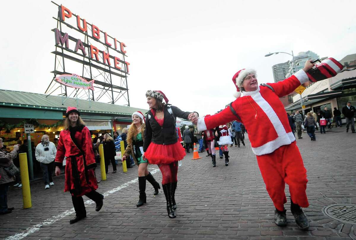 Santas dance as they make their way past the Public Market sign at Pike Place Market during SantaCon 2012 in Seattle on Saturday, December 8, 2012.