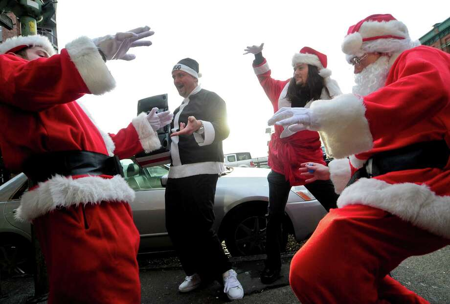 A group of Santas get funky outside the Sarajevo Lounge during SantaCon 2012 in Seattle on Saturday, December 8, 2012. The crawl began at noon at Seattle Center and wove throughout Belltown, Capitol Hill, Westlake and Pacific Place, finally ending around 2 a.m. downtown. Photo: LINDSEY WASSON, Lindsey Wasson / SEATTLEPI.COM