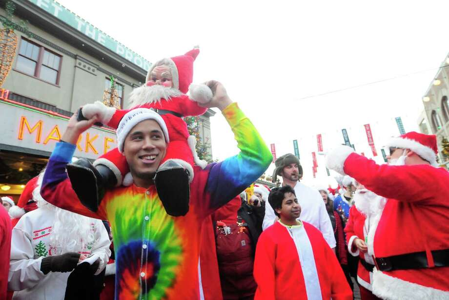 "Craig Liste gives ""Dirty Santa"" a ride during SantaCon 2012 at Pike Place Market in Seattle on Saturday, December 8, 2012.  Photo: LINDSEY WASSON, Lindsey Wasson / SEATTLEPI.COM"