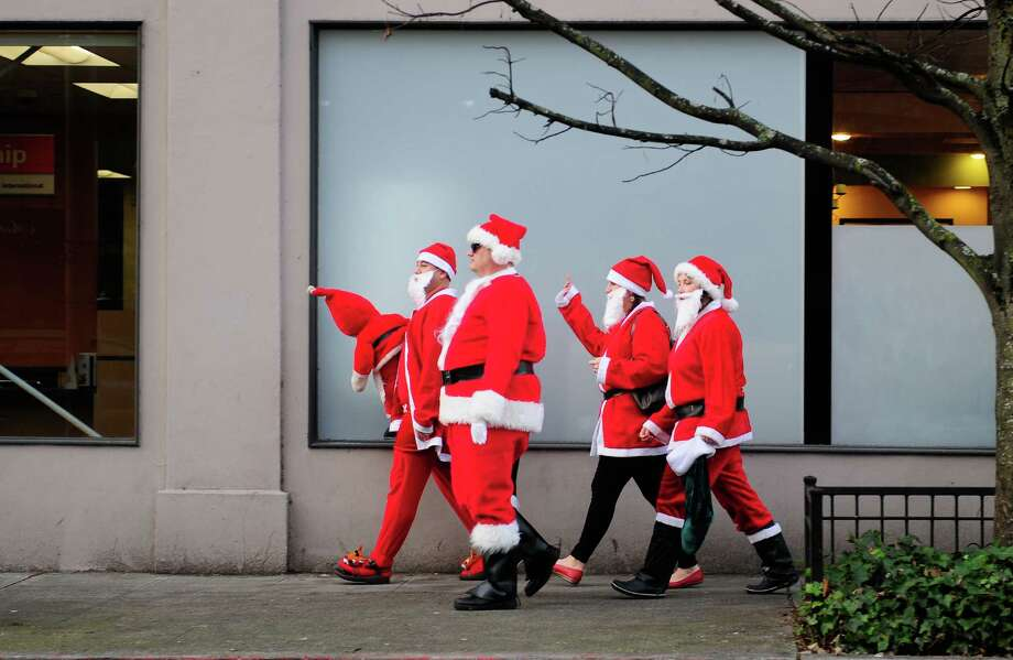 A group of Santas walk down Cedar St. on the way to their next stop during SantaCon 2012 in Seattle on Saturday, December 8, 2012.  Photo: LINDSEY WASSON, Lindsey Wasson / SEATTLEPI.COM