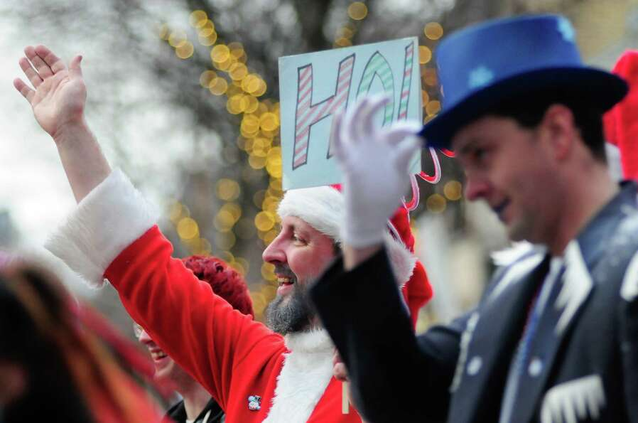 SantaCon participants wave at passing cars during SantaCon 2012 in Seattle on Saturday, December 8,