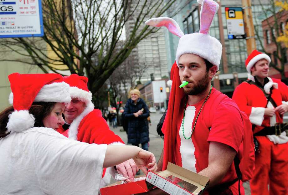 SantaCon organizer Dave LeClair hands out candy canes in the parking lot near Belltown Pub during SantaCon 2012 in Seattle on Saturday, December 8, 2012.  Photo: LINDSEY WASSON, Lindsey Wasson / SEATTLEPI.COM