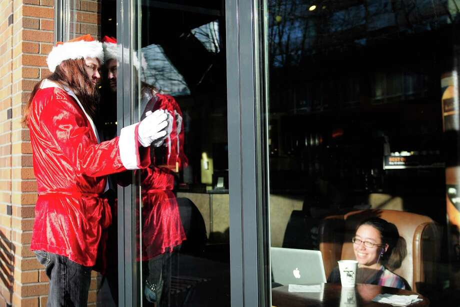A SantaCon participant says hello to patrons of Uptown Espresso during SantaCon 2012 in Seattle on Saturday, December 8, 2012.  Photo: LINDSEY WASSON, Lindsey Wasson / SEATTLEPI.COM