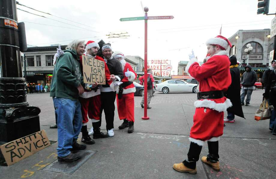 A few Santas take a photograph with a man who is asking for weed during SantaCon 2012 in Seattle on Saturday, December 8, 2012.  Photo: LINDSEY WASSON, Lindsey Wasson / SEATTLEPI.COM