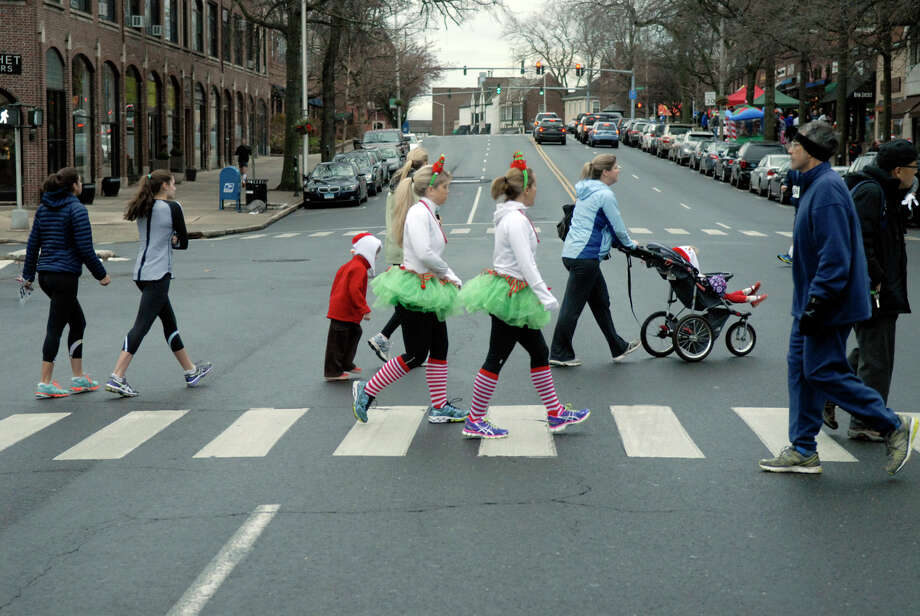 Jessica McCluskey, left, and Christine Sikes channel elves as they make their way to the start of the race as the Volvo of Stamford Greenwich Cup series of 10 races wraps up with the three mile Jingle Bell Jog on Church Street in Greenwich, Conn., Dec. 9, 2012. The event was run by Threads and Treads and raised money for Pathways, Inc., a town agency aimed at helping people who suffer from chronic mental illness. Photo: Keelin Daly / Stamford Advocate Riverbend Stamford, CT