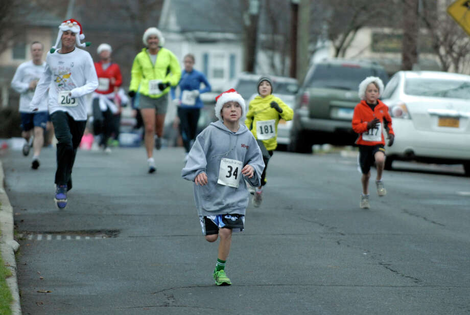 Fritz Conrod, 10, cruises to the finish as the Volvo of Stamford Greenwich Cup series of 10 races wraps up with the three mile Jingle Bell Jog on Church Street in Greenwich, Conn., Dec. 9, 2012. The event was run by Threads and Treads and raised money for Pathways, Inc., a town agency aimed at helping people who suffer from chronic mental illness. Photo: Keelin Daly / Stamford Advocate Riverbend Stamford, CT