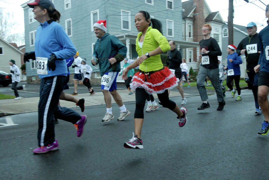 Mae Vargas runs in style as the Volvo of Stamford Greenwich Cup series of 10 races wraps up with the three mile Jingle Bell Jog on Church Street in Greenwich, Conn., Dec. 9, 2012. The event was run by Threads and Treads and raised money for Pathways, Inc., a town agency aimed at helping people who suffer from chronic mental illness. Photo: Keelin Daly / Stamford Advocate Riverbend Stamford, CT