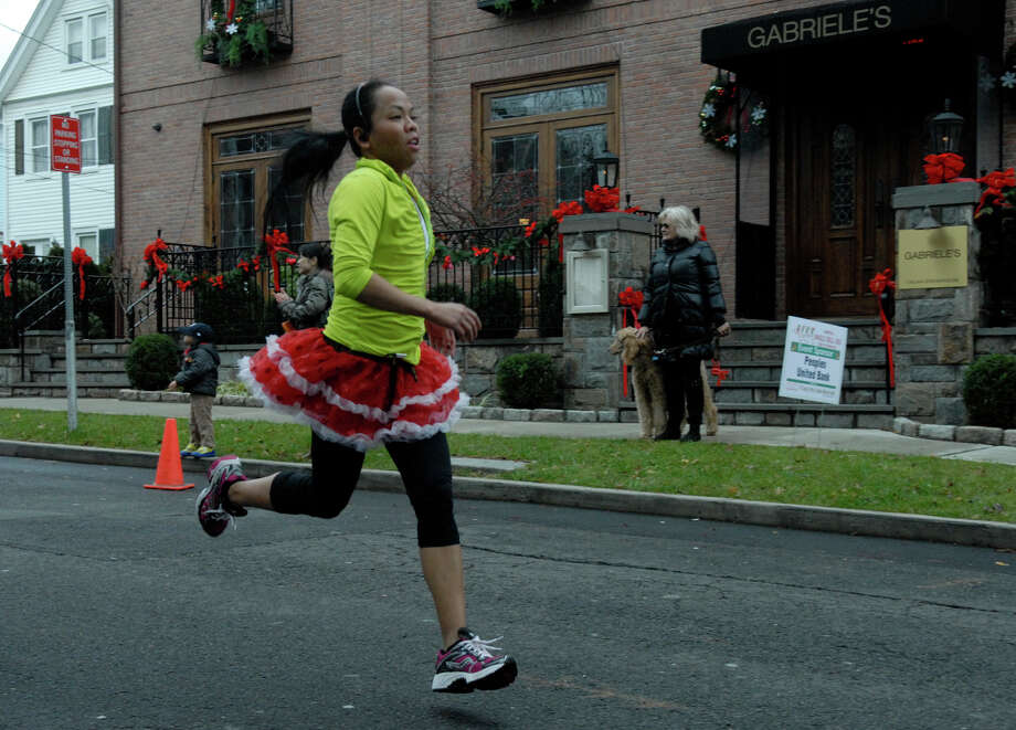 Mae Vargas finishes in style as the Volvo of Stamford Greenwich Cup series of 10 races wraps up with the three mile Jingle Bell Jog on Church Street in Greenwich, Conn., Dec. 9, 2012. The event was run by Threads and Treads and raised money for Pathways, Inc., a town agency aimed at helping people who suffer from chronic mental illness. Photo: Keelin Daly / Stamford Advocate Riverbend Stamford, CT