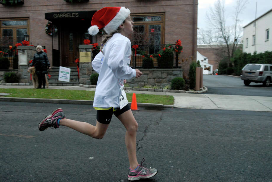 Caroline Conrad, 12, finishes as the Volvo of Stamford Greenwich Cup series of 10 races wraps up with the three mile Jingle Bell Jog on Church Street in Greenwich, Conn., Dec. 9, 2012. The event was run by Threads and Treads and raised money for Pathways, Inc., a town agency aimed at helping people who suffer from chronic mental illness. Photo: Keelin Daly / Stamford Advocate Riverbend Stamford, CT