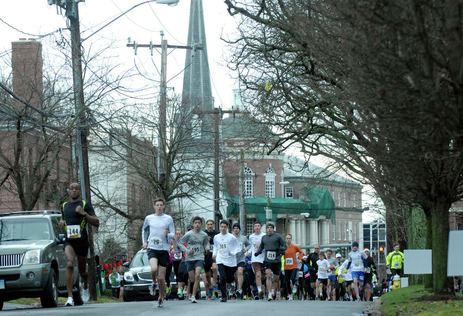 Alan Wells, left, sets the pace as the Volvo of Stamford Greenwich Cup series of 10 races wraps up with the three mile Jingle Bell Jog on Church Street in Greenwich, Conn., Dec. 9, 2012. The event was run by Threads and Treads and raised money for Pathways, Inc., a town agency aimed at helping people who suffer from chronic mental illness. Photo: Keelin Daly / Stamford Advocate Riverbend Stamford, CT