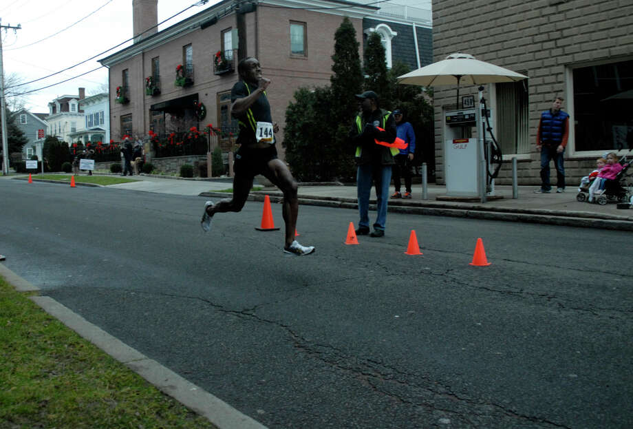 Alan Wells finishes first as the Volvo of Stamford Greenwich Cup series of 10 races wraps up with the three mile Jingle Bell Jog on Church Street in Greenwich, Conn., Dec. 9, 2012. The event was run by Threads and Treads and raised money for Pathways, Inc., a town agency aimed at helping people who suffer from chronic mental illness. Photo: Keelin Daly / Stamford Advocate Riverbend Stamford, CT