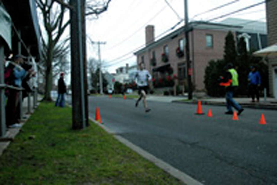 Kenner Clark finishes second as the Volvo of Stamford Greenwich Cup series of 10 races wraps up with the three mile Jingle Bell Jog on Church Street in Greenwich, Conn., Dec. 9, 2012. The event was run by Threads and Treads and raised money for Pathways, Inc., a town agency aimed at helping people who suffer from chronic mental illness. Photo: Keelin Daly / Stamford Advocate Riverbend Stamford, CT