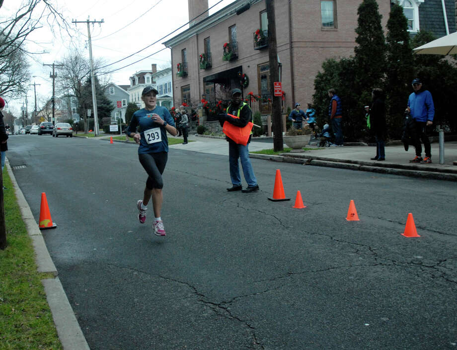 Liz Herbert finishes second for the women as the Volvo of Stamford Greenwich Cup series of 10 races wraps up with the three mile Jingle Bell Jog on Church Street in Greenwich, Conn., Dec. 9, 2012. The event was run by Threads and Treads and raised money for Pathways, Inc., a town agency aimed at helping people who suffer from chronic mental illness. Photo: Keelin Daly / Stamford Advocate Riverbend Stamford, CT