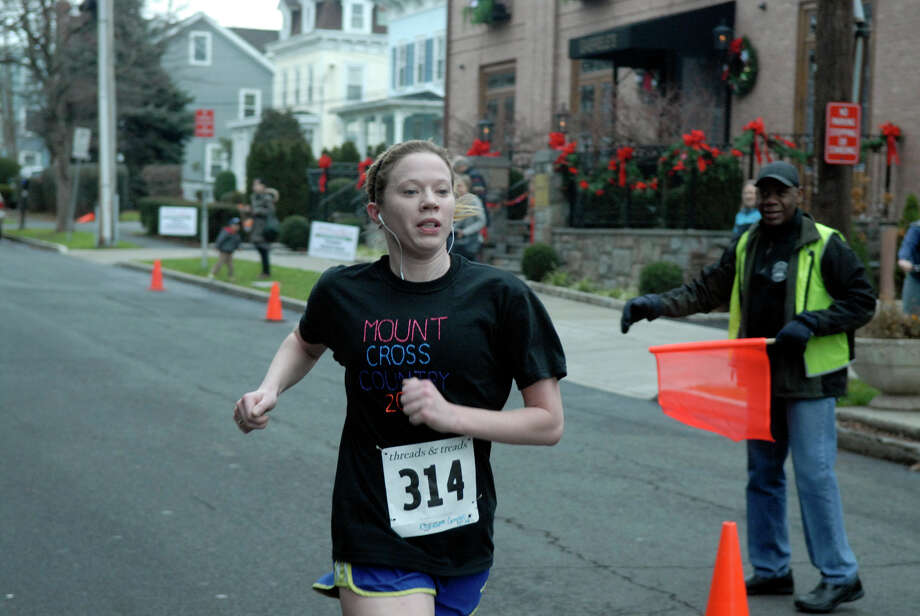 Liz Campbell finishes third for the women as the Volvo of Stamford Greenwich Cup series of 10 races wraps up with the three mile Jingle Bell Jog on Church Street in Greenwich, Conn., Dec. 9, 2012. The event was run by Threads and Treads and raised money for Pathways, Inc., a town agency aimed at helping people who suffer from chronic mental illness. Photo: Keelin Daly / Stamford Advocate Riverbend Stamford, CT