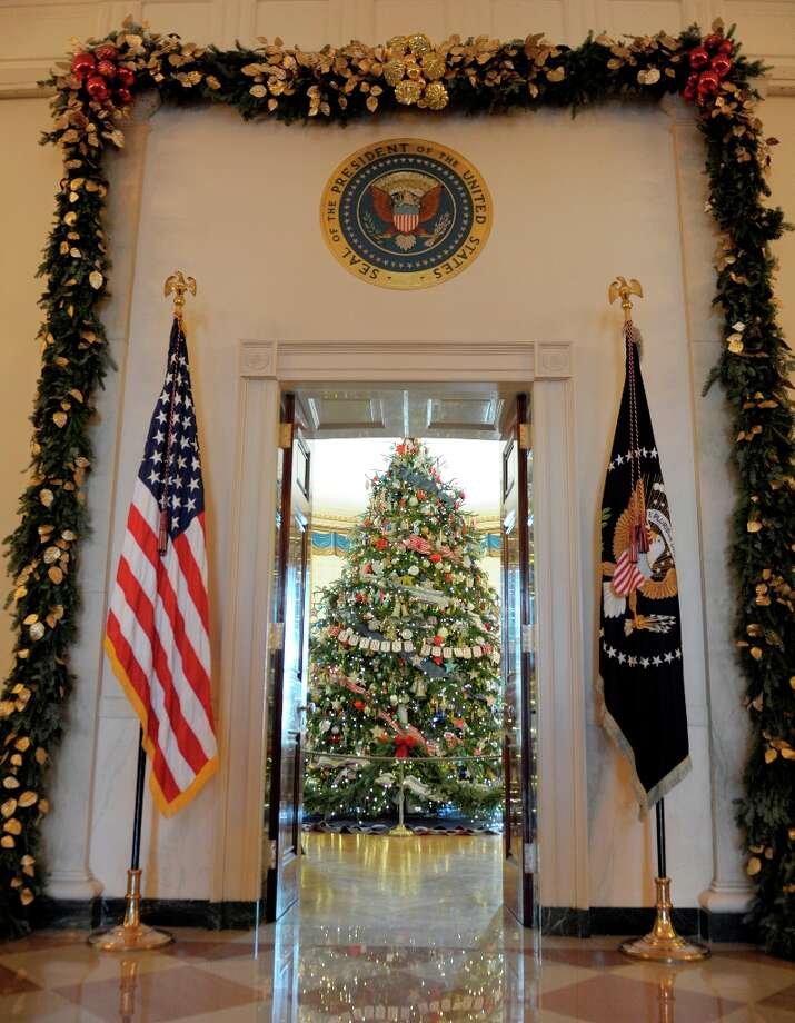 The official White House Christmas tree, an 18-foot-6-inch Frasier fur from Jefferson, N.C., trimmed with ornaments decorated by children of military families, sits in the Blue Room of the White House in Washington, Wednesday, Nov. 28, 2012, during a preview of the White House holiday decorations. The theme for the White House Christmas 2012 is Joy to All. (Susan Walsh / AP Photo) Photo: Susan Walsh, Associated Press / AP