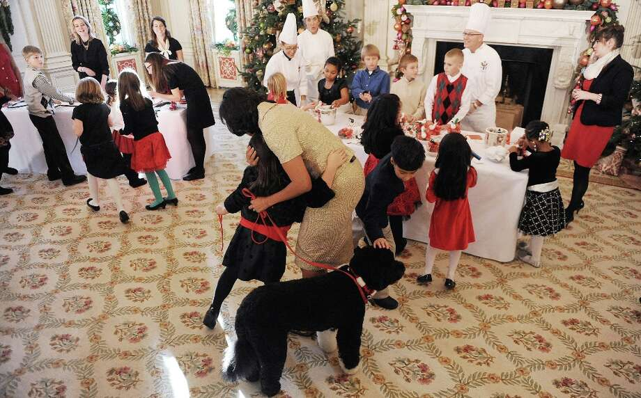 First lady Michelle Obama and family dog Bo are greeted by children during the preview of the White House Christmas decorations, November 28, 2012, in Washington, D.C. Photo: Olivier Douliery, McClatchy-Tribune News Service / Abaca Press