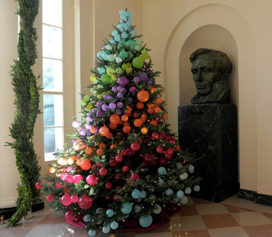 A Christmas tree decorated in a rainbow of colors sits next to a statue of President Lincoln in the East Garden Room of the White House in Washington, Wednesday, Nov. 28, 2012. The theme for the White House Christmas 2012 is Joy to All. (Susan Walsh / AP Photo) Photo: Susan Walsh, Associated Press / AP