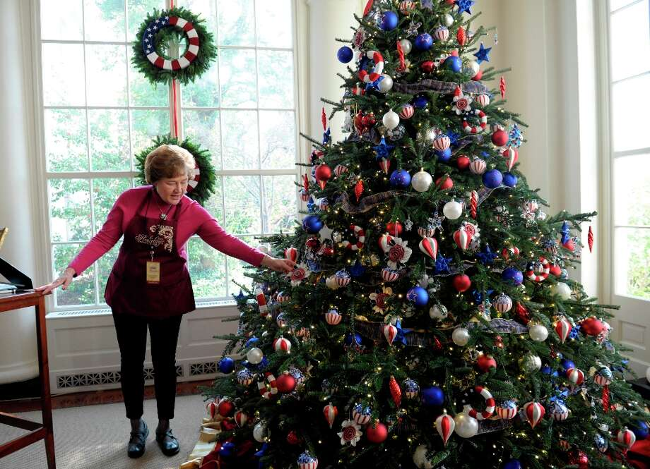 Volunteer Paulette Marini describes the decorations on the tree in the East Landing of White House in Washington, Wednesday, Nov. 28, 2012, during a preview of the holiday deocrations. The decorations pay tribute to the Armed Forces and their families. The theme for the White House Christmas 2012 is Joy to All. (AP Photo/Susan Walsh) (Susan Walsh / AP Photo) Photo: Susan Walsh, Associated Press / AP