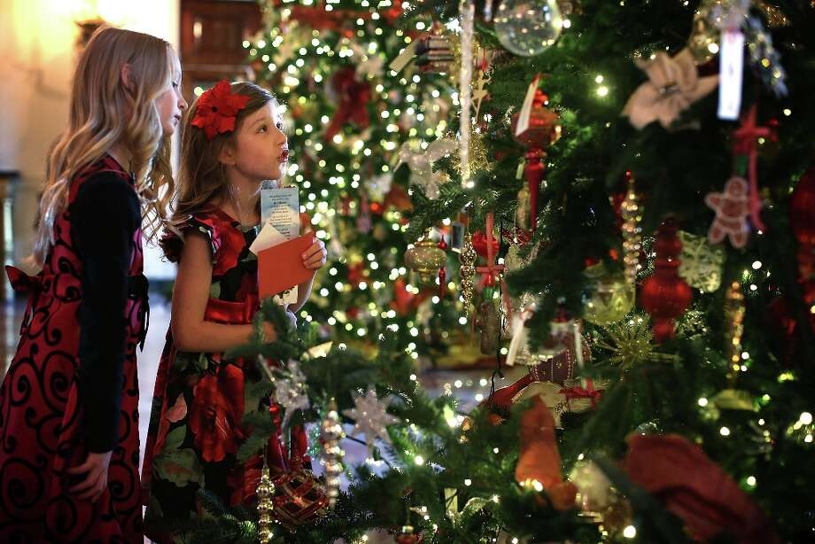 Lauren Ray (L) and Olivia Marlow (2nd L) of Northern Virginia look at ornaments on a Christmas tree during a preview of the 2012 White House holiday decorations November 28, 2012 at the White House in Washington, DC. The first lady welcomed military families, including Gold Star and Blue Star parents, spouses and children, to the White House for the first viewing of the 2012 holiday decorations. Photo: Alex Wong, Getty Images / 2012 Getty Images