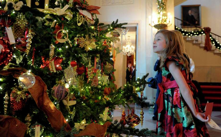 Olivia Marlow, 6, looks at a tree honoring presidential first ladies that is on display in the Grand Foyer of the White House in White House in Washington, Wednesday, Nov. 28, 2012, during a preview of the holiday decorations. The theme for the White House Christmas 2012 is Joy to All.  (Susan Walsh / AP Photo) Photo: Susan Walsh, Associated Press / AP
