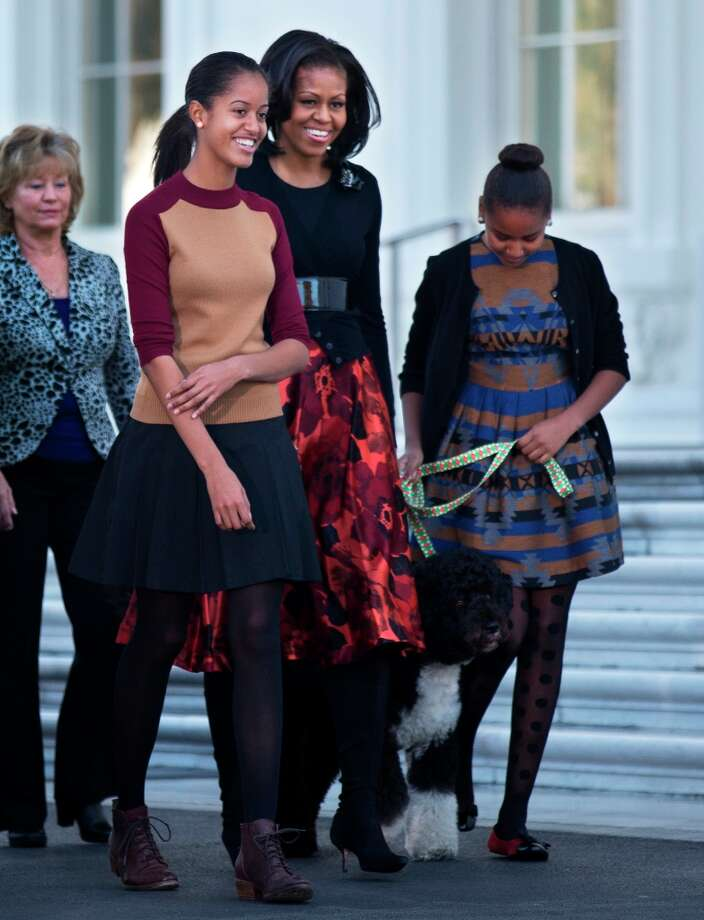 First lady Michelle Obama, with daughters Sasha and Malia, left, and first dog Bo, walk on the North Portico of the White House in Washington, Friday, Nov. 23, 2012, where they received the official White House Christmas tree, a 19-foot Fraser Fir from Jefferson, N.C. (Manuel Balce Ceneta / AP Photo) Photo: Manuel Balce Ceneta, Associated Press / AP