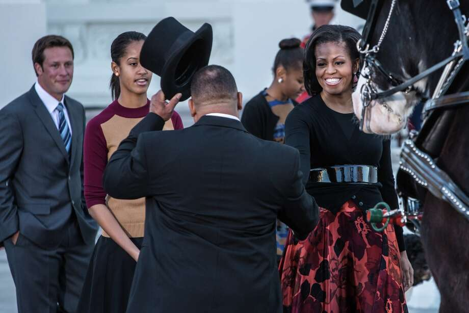 First lady Michelle Obama (R) and her daughter Malia Obama (2nd L) are presented with the official White House Christmas Tree on November 23, 2012 in Washington, DC. The tree is a 19-foot Fraser Fir from Peak Farms in North Carolina, which is owned by Rusty and Beau Estes. Photo: Brendan Hoffman, Getty Images / 2012 Getty Images