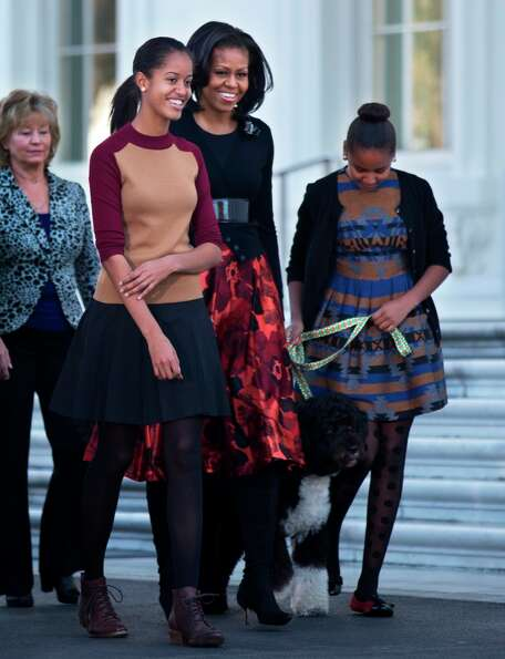 First lady Michelle Obama, with daughters Sasha and Malia, left, and first dog Bo, walk on the North