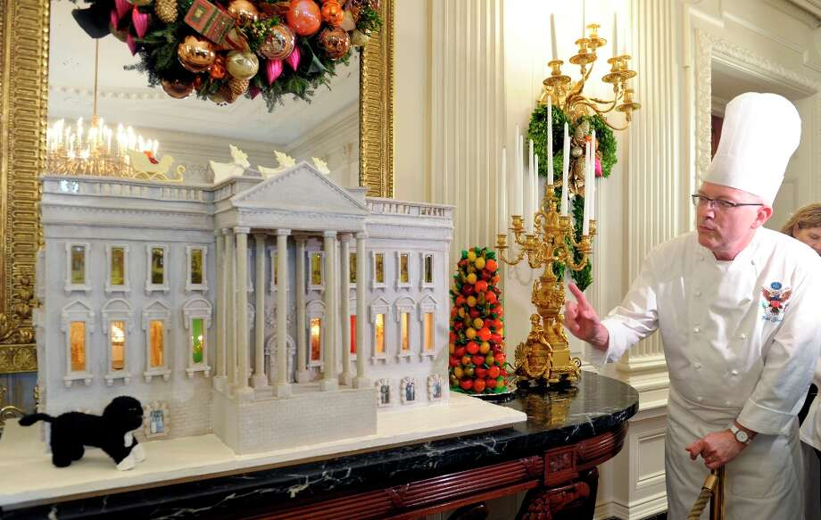 White House Pastry Chef Bill Yosses explains his design for the nearly 300-pound gingerbread house of the White House, on display in the State Dining Room of the White House in Washington, Wednesday, Nov. 28, 2012. The house features Bo, the Obama family dog, left,  a vegetable garden and views inside the White House. The theme for the White House Christmas 2012 is Joy to All. The White House gingerbread house has been a tradition since the 1960s. (Susan Walsh / AP Photo) Photo: Susan Walsh, Associated Press / AP