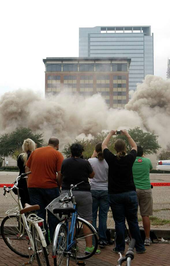 Trying to capture an image of history with their cameras, people look on as the more than 80 year-old 10-story Ben Milam hotel building at 1717 Texas St. that served as a home away from home for travelers arriving at Union Station was imploded Sunday, Dec. 9, 2012, in Houston. 
