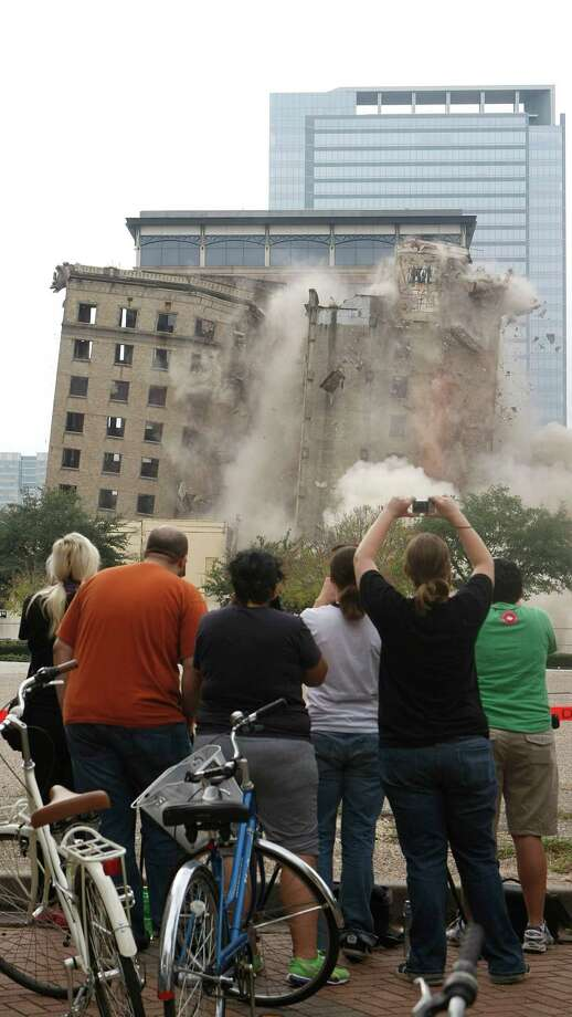 Trying to capture an image of history with their cameras, people look on as the more than 80 year-old 10-story Ben Milam hotel building at 1717 Texas St. that served as a home away from home for travelers arriving at Union Station was imploded Sunday, Dec. 9, 2012, in Houston.  The Finger Cos. is planning luxury apartments on two downtown blocks - one of which includes the old hotel. The implosion for that type of building could cost as much as $200,000, said Larry Grisham, senior vice president of demolition firm JTB Services. That's just for the implosion. Prep work and clearing the property could more than double the price, he said.  The Ben Milam Hotel was built around 1926 by Houston attorneys John Crooker and R. Clarence Fulbright, architectural historian Stephen Fox said. The building's architect was James Ruskin Bailey, whose projects include downtown's Public National Bank Building at 402 Main and the now-demolished Hotel Beaumont in Beaumont. Photo: Johnny Hanson, Houston Chronicle / © 2012  Houston Chronicle