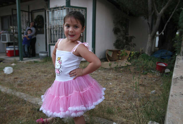 Five-year-old Anahi Perales plays in front of her uncle's house in Carrizo Springs, Texas, Tuesday, Dec. 4, 2012. Her mother, Dulce Garcia, in back, moved her family in with her brother a year ago. Housing in the Eagle Ford Shale counties is in high demand and expensive. Photo: Jerry Lara, San Antonio Express-News / © 2012 San Antonio Express-News