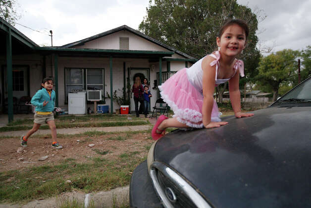 Five-year-old Anahi Perales, right, and her sister, Faith Perales, 6, left, play in front of their uncle's house in Carrizo Springs, Texas, Tuesday, Dec. 4, 2012. Dulce Garcia, the children's mother, moved the family in with her brother a year ago. Housing in the Eagle Ford Shale counties is in high demand and expensive. Photo: Jerry Lara, San Antonio Express-News / © 2012 San Antonio Express-News