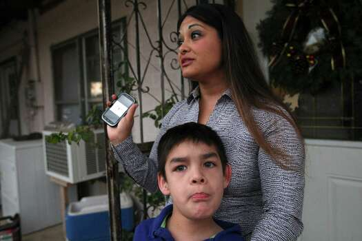 Dulce Garcia, 33, holds her son, Jacob Casillas, 11, in front of her brother's house in Carrizo Springs, Texas, Tuesday, Dec. 4, 2012. Garcia moved her family in with her brother a year ago. Housing in the Eagle Ford Shale counties is in high demand and expensive. She is in the process of buying a house through a government program. Photo: Jerry Lara, San Antonio Express-News / © 2012 San Antonio Express-News