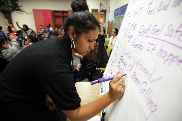 Sierra Luna of United Communities of San Antonio writes comments from students during an anti-bullying, anti-bigotry workshop for fifth graders at Candlewood Elementary. Photo: Bob Owen, San Antonio Express-News / © 2012 San Antonio Express-News
