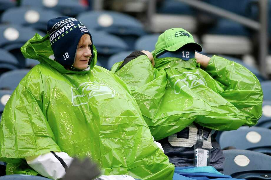 Seattle Seahawks fans prepare for rain while watching warm ups before an NFL football game between the Seattle Seahawks and the Arizona Cardinals in Seattle, Sunday, Dec. 9, 2012. Photo: AP