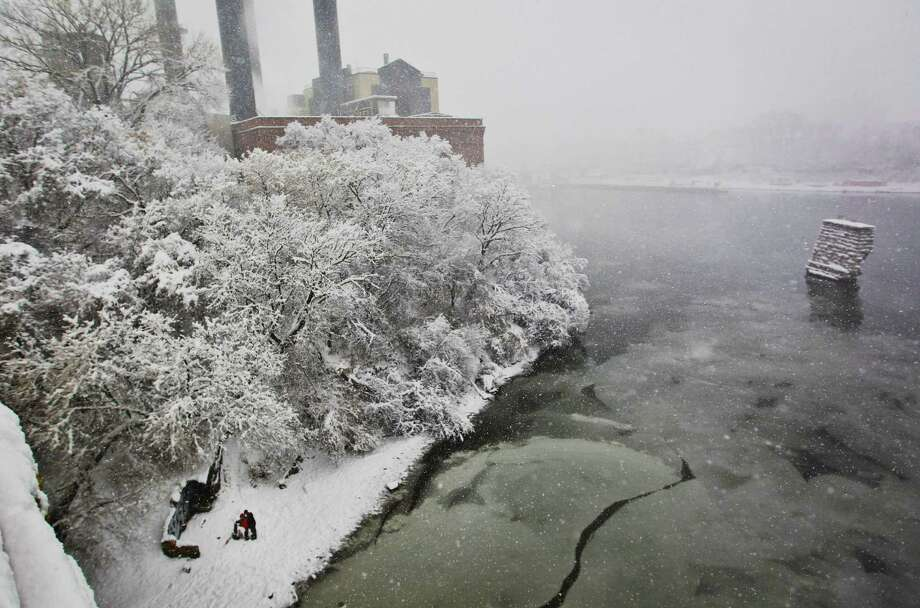 Julie Strenkowski and Phil Wolf kiss under the Stone Arch Bridge on the banks of the Mississippi River, in Minneapolis. A major winter storm is expected to dump 9 to 15 inches across a broad belt of central Minnesota including the Twin Cities area by Sunday night, and the storm was also to bring heavy snow to parts of western Wisconsin. (AP Photo/The Star Tribune, Renee Jones Schneider)  MANDATORY CREDIT; ST. PAUL PIONEER PRESS OUT; MAGS OUT; TWIN CITIES TV OUT Photo: Renee Jones Schneider, Associated Press / The Star Tribune